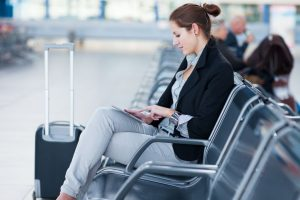 14108915 - young female passenger at the airport, using her tablet computer while waiting for her flight (color toned image)