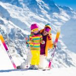 63589457 - family ski vacation. group of skiers in swiss alps mountains. mother and child skiing in winter. parents teach kids alpine downhill skiing. ski gear and wear, safe helmets.